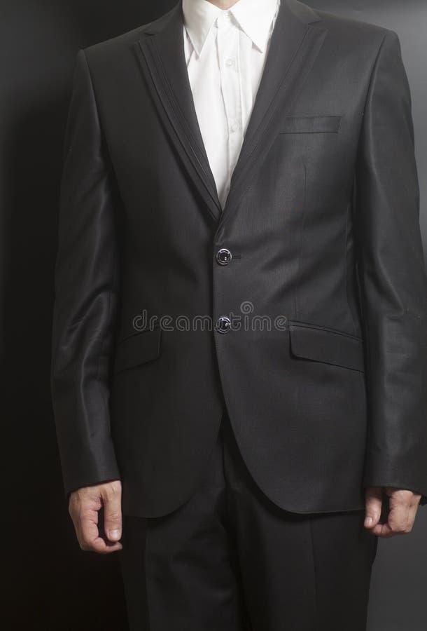 Человек в черном костюме и белой рубашке стоковые изображения