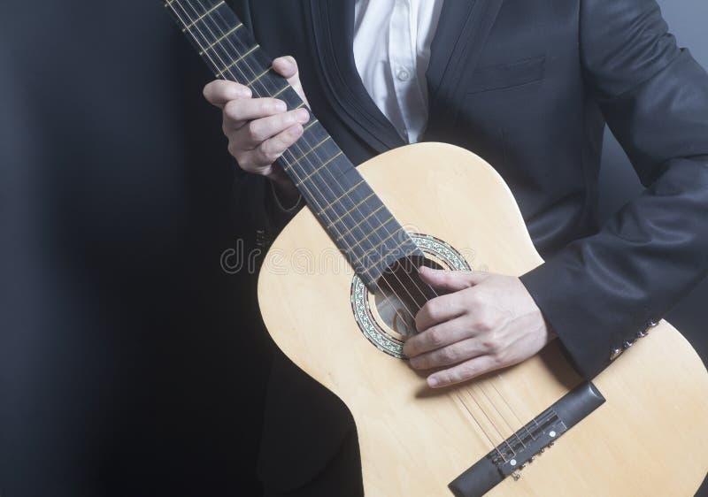 Человек в черном костюме с акустической классической гитарой стоковое фото rf