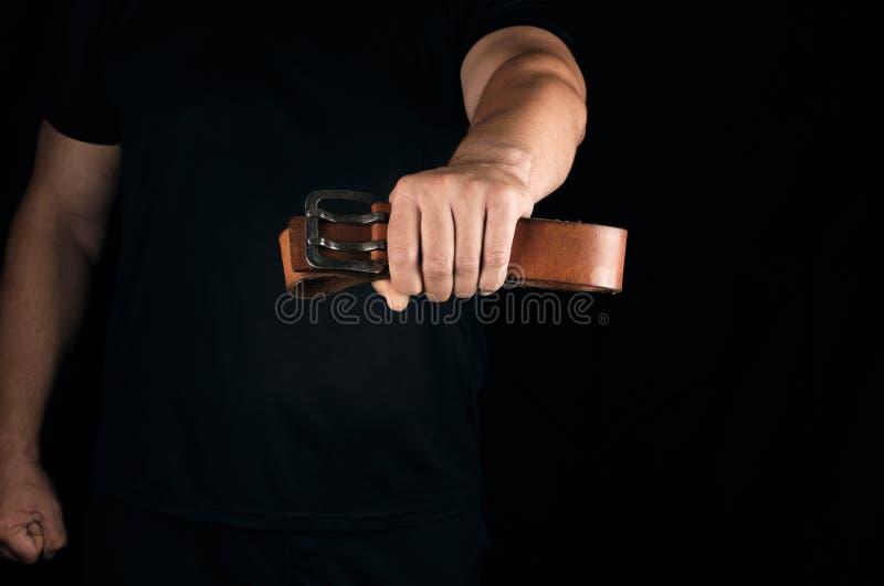 Человек в черных одеждах держит коричневый кожаный пояс с пряжкой стоковая фотография rf