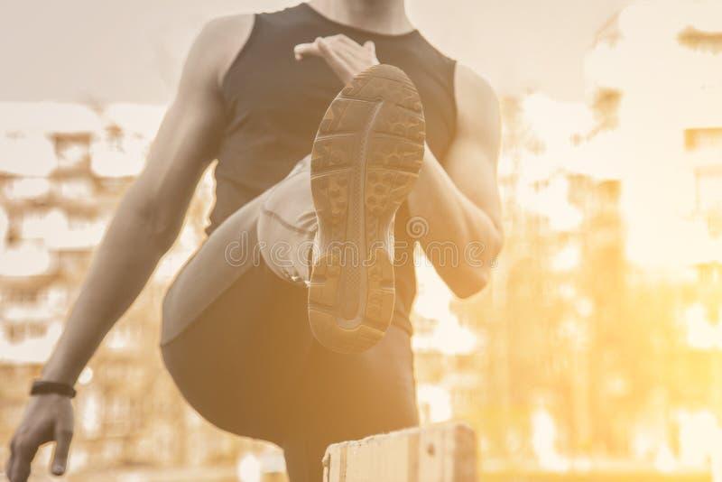 Человек в черных одеждах работает outdoors с барьером спортсмен фитнеса на спортивной площадке тренировка с барьером E стоковая фотография rf