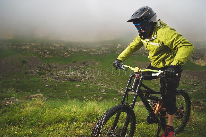 Человек в шлеме горы ехать горный велосипед едет вокруг красивой природы в пасмурной погоде покато стоковое фото