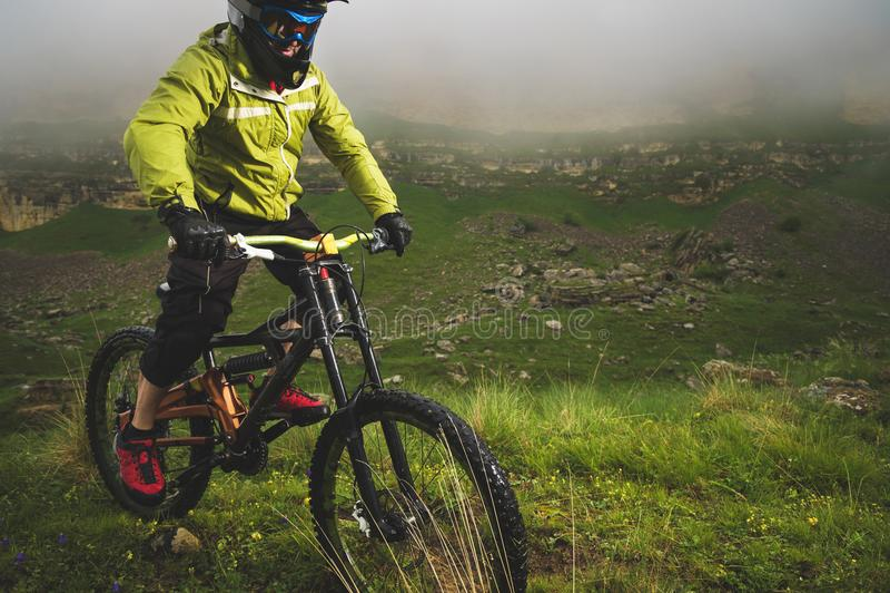 Человек в шлеме горы ехать горный велосипед едет вокруг красивой природы в пасмурной погоде покато стоковое изображение rf