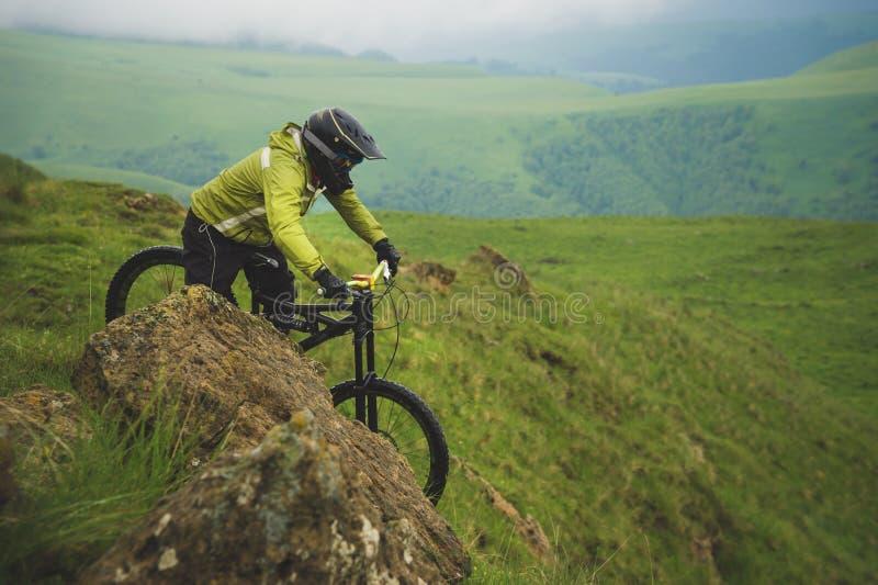 Человек в шлеме горы ехать горный велосипед едет вокруг красивой природы в пасмурной погоде покато стоковые фотографии rf