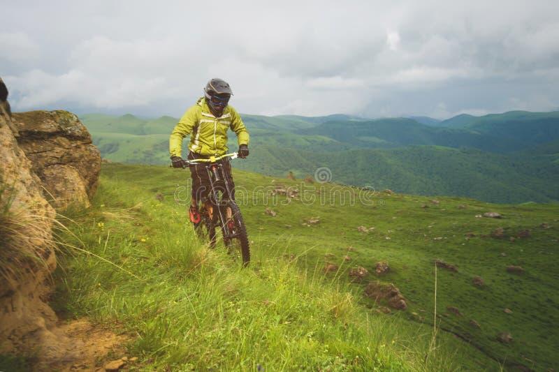 Человек в шлеме горы ехать горный велосипед едет вокруг красивой природы в пасмурной погоде покато стоковая фотография