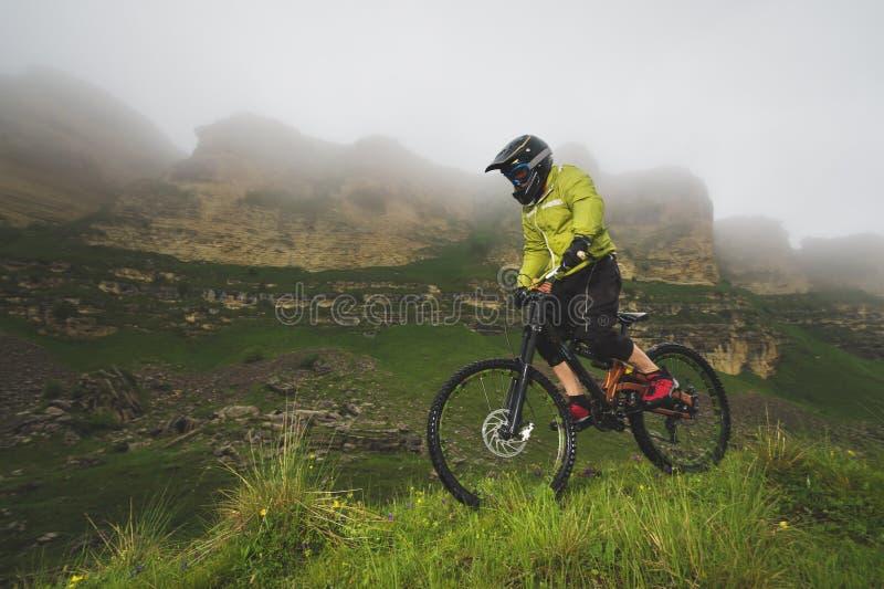 Человек в шлеме горы ехать горный велосипед едет вокруг красивой природы в пасмурной погоде покато стоковые изображения