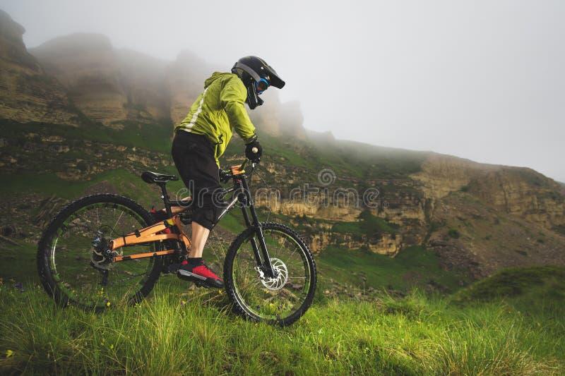 Человек в шлеме горы ехать горный велосипед едет вокруг красивой природы в пасмурной погоде покато стоковое изображение