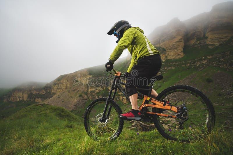 Человек в шлеме горы ехать горный велосипед едет вокруг красивой природы в пасмурной погоде покато стоковая фотография rf