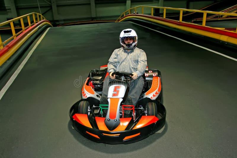 Человек в шлеме в идет-kart на karting-след внутри помещения стоковое изображение rf