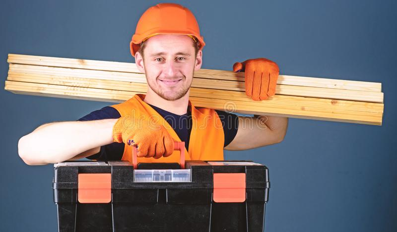 Человек в шлеме, трудная шляпа держит toolbox и деревянные балки, серую предпосылку Плотник, лейборист, построитель, woodworker д стоковое фото