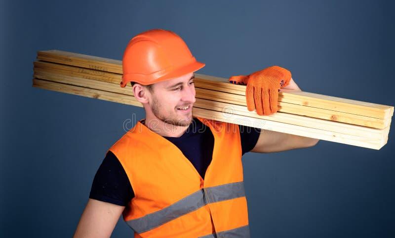 Человек в шлеме, трудной шляпе и защитных перчатках держит деревянную балку, серую предпосылку Плотник, woodworker, лейборист стоковые фотографии rf