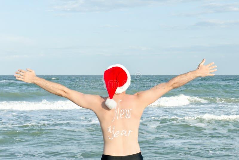 Человек в шляпах Санты с Новым Годом надписи на задней части на t стоковое фото