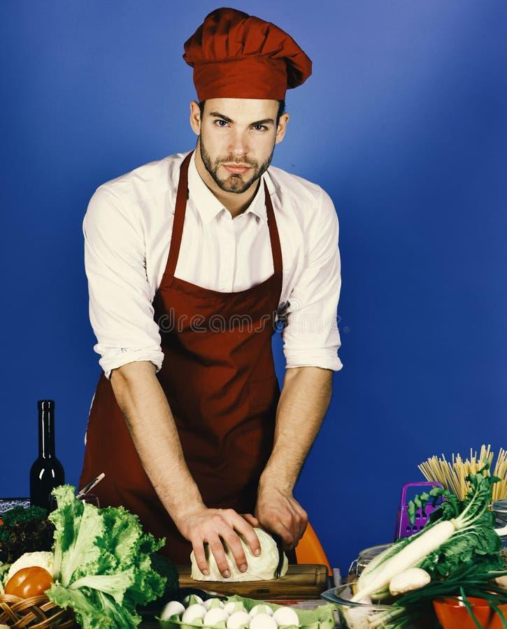 Человек в шляпе и рисберме кашевара режет капусту Кашевар работает в кухне около таблицы с овощами и инструментами стоковая фотография rf