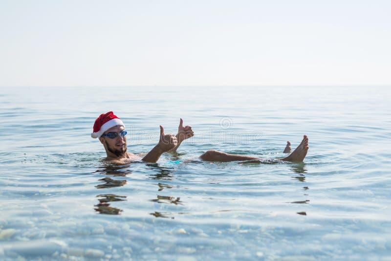 Человек в шляпе и стеклах Санта Клауса для плавать, предпосылка рождества Ослабьте в тропических странах в зиме, Новом Годе стоковые фото