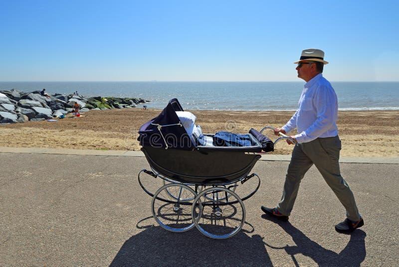 Человек в шляпе нажимая винтажный Pram вдоль прогулки набережной стоковые фотографии rf
