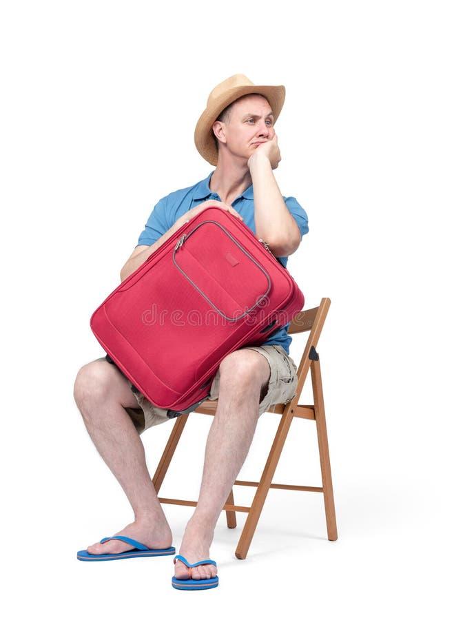Человек в шляпе, футболке, шортах и тапочках, сидящ на стуле, ожидание, обнимая чемодан r стоковые изображения rf