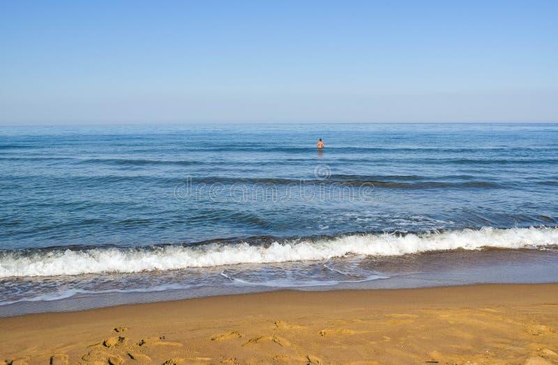 Человек в штиле на море стоковые фото