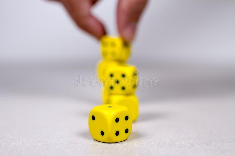 Человек глубины поля укомплектовывает личным составом руку штабелируя вверх по желтой кости на заднем плане стоковые фотографии rf