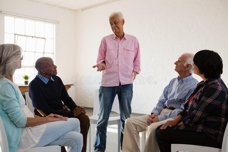 Человек говоря к друзьям сидя на стуле стоковое фото rf