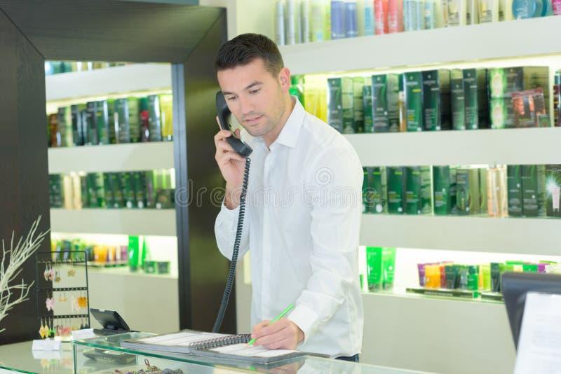 Человек говоря на мобильном телефоне на салоне парикмахеров стоковое фото rf