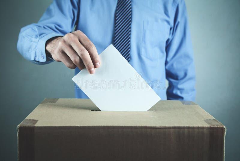 Человек голосуя на урне для избирательных бюллетеней Концепция избрания и демократии стоковые изображения