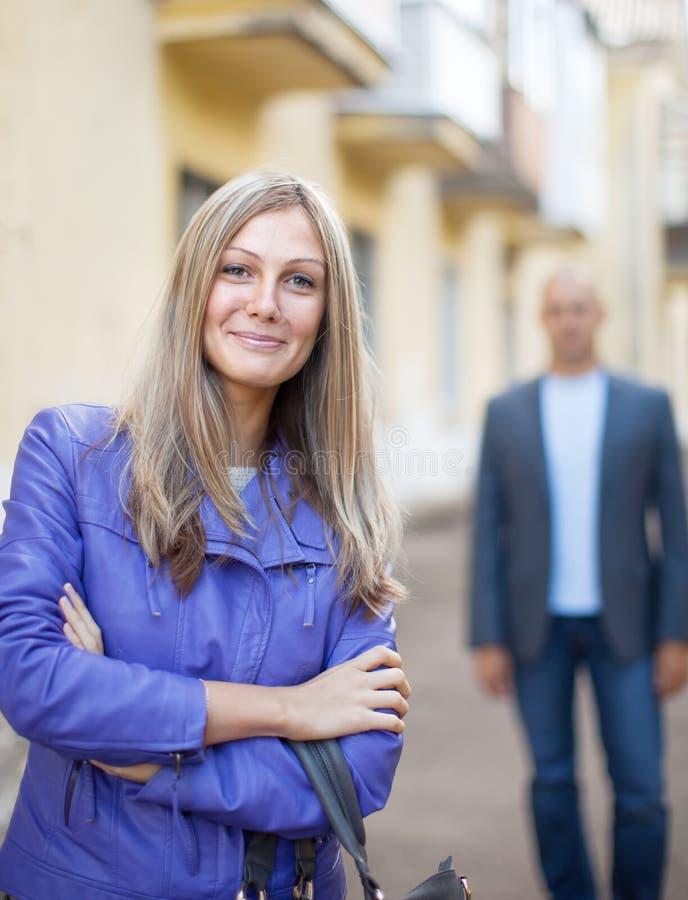 Человек гуляет за женщиной на улице стоковое изображение