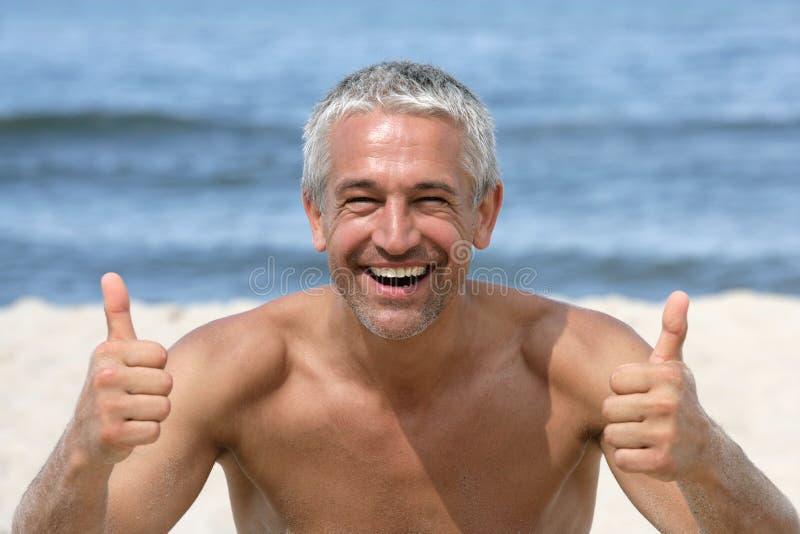 Человек давая большие пальцы руки вверх на пляже стоковые фотографии rf