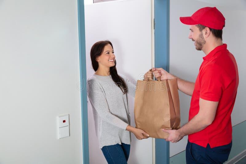 Человек давая бумажный мешок женщине стоковая фотография