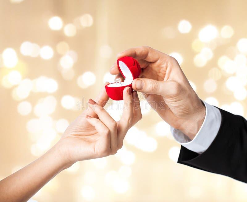 Человек давая кольцо с бриллиантом женщине на день Святого Валентина стоковые фотографии rf
