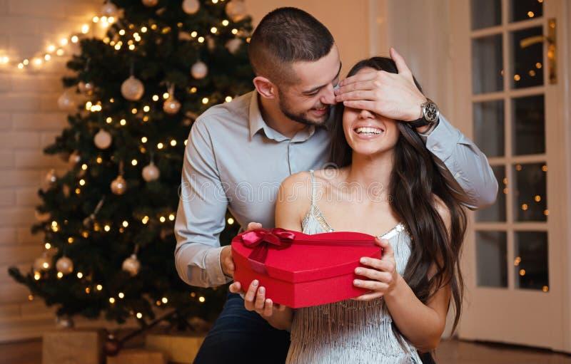 Человек давая подарок на рождество к его подруге стоковое изображение