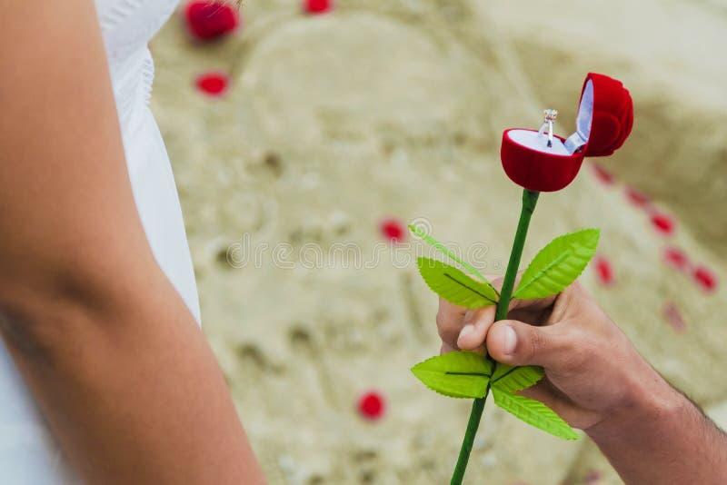 Человек давая подарочную коробку с обручальным кольцом к женщине стоковое изображение