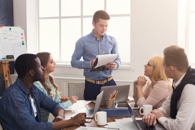 Человек давая представление к коллегам в офисе стоковое изображение rf