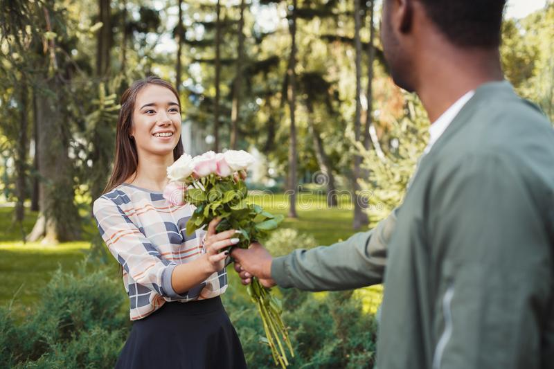Человек давая цветки для его красивой подруги стоковое фото rf