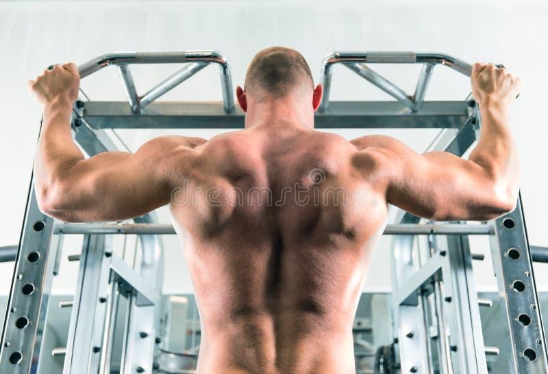 Человек делает его разминку в спортзале стоковая фотография