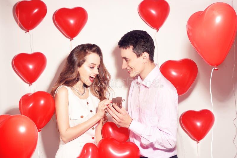Человек делает настоящий момент к его симпатичной девушке возлюбленн День Валентайн любовника Пары валентинки Мальчик дает к его  стоковое изображение