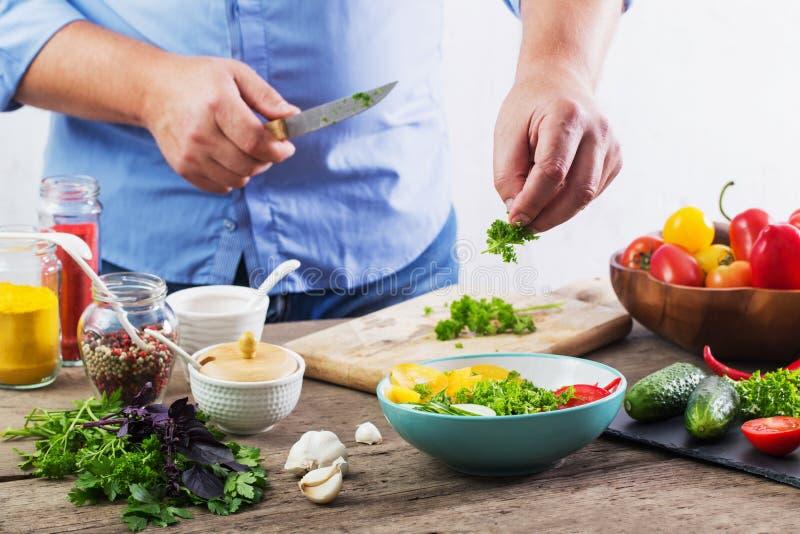 Человек делая вегетарианский салат стоковое изображение