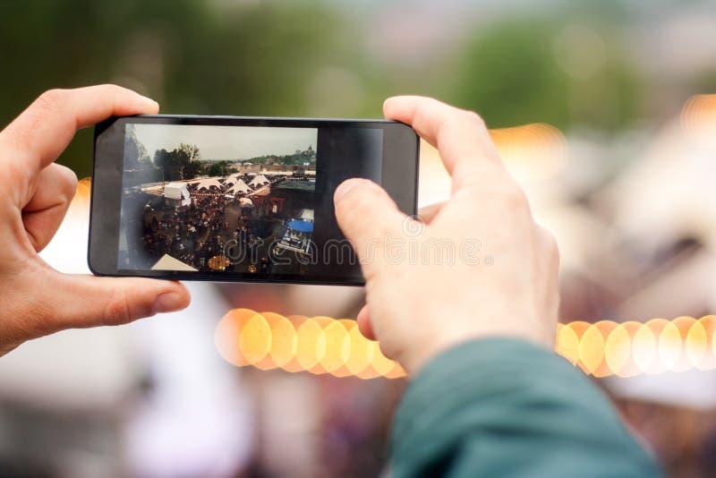 Человек делая изображение в улице с сотовым телефоном Предпосылка bokeh фестиваля улицы стоковые фото