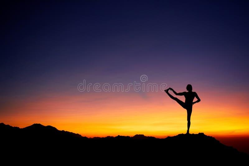 Человек делая йогу на небе захода солнца стоковое фото rf