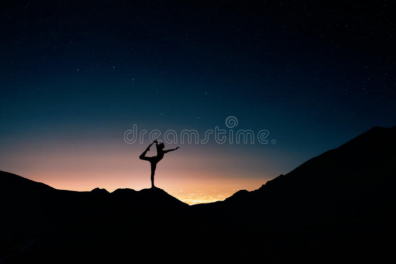 Человек делая йогу на ночном небе стоковое изображение rf