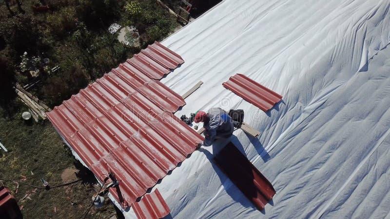 Человек делая крышу загородного дома r Взгляд сверху построителя кладя гонт металла на крышу Человек независимо стоковое изображение