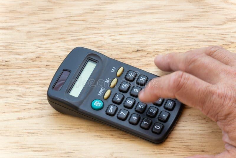 человек делая счет, в калькуляторе кармана с деревянной предпосылкой стоковое фото
