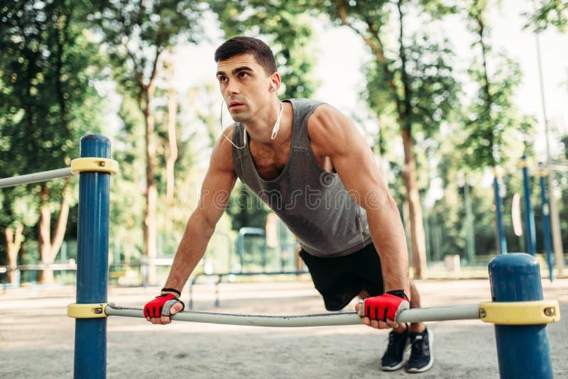 Человек делая тренировку нажима-вверх используя турник стоковые фото