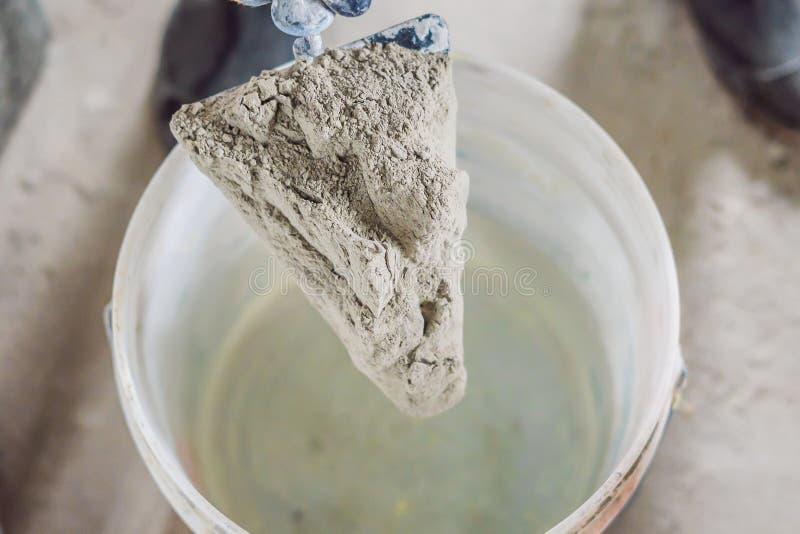 Человек делая цемент со смесителем конструкции в ведре стоковое изображение rf