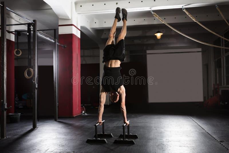 Человек делая Handstand на параллельном баре стоковая фотография