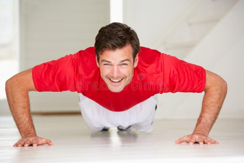 Человек делая push-ups в домашней гимнастике стоковое изображение rf