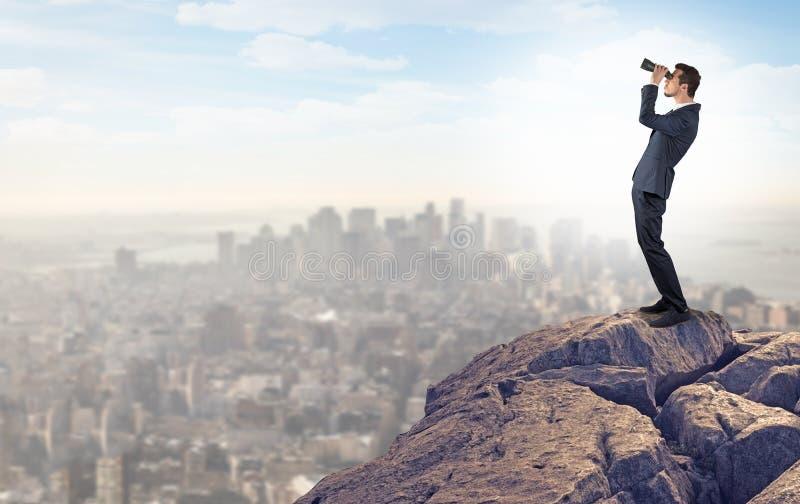 Человек дела смотря к городу от расстояния стоковое фото