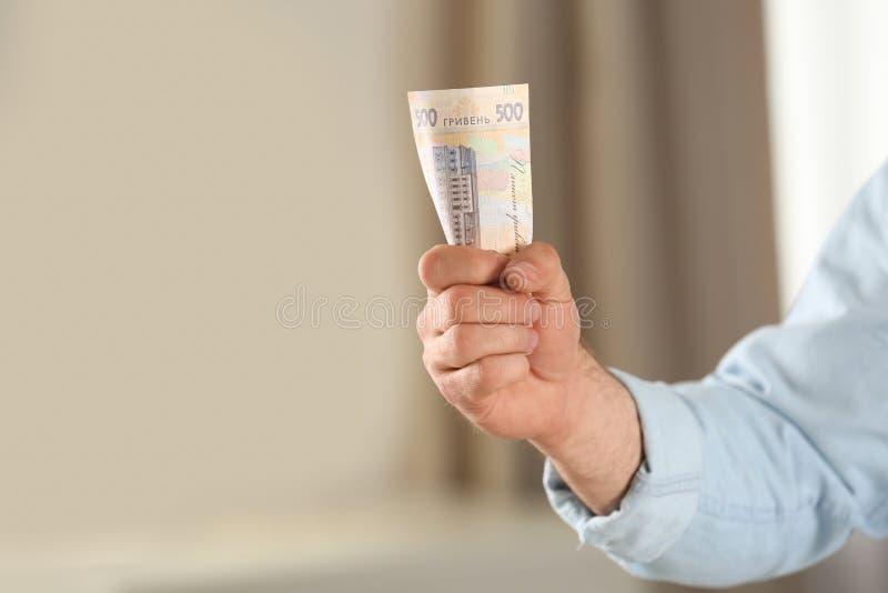 Человек держа банкноту 500 украинскую гривен против запачканной предпосылки, крупного плана Международные отношения стоковые фото