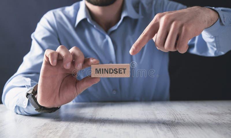 Человек держа деревянный блок mindset r стоковая фотография