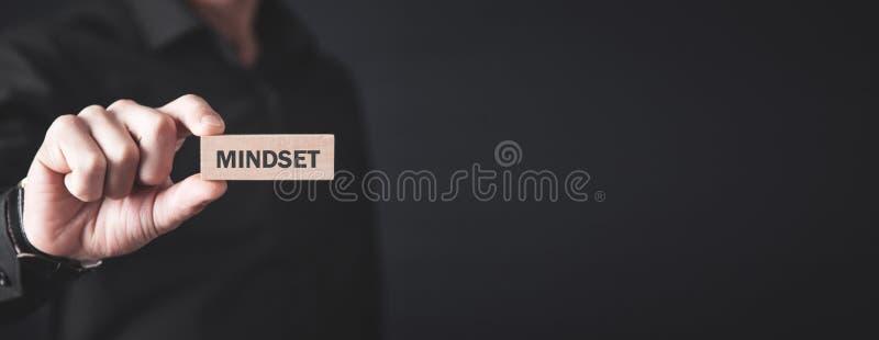 Человек держа деревянный блок mindset r стоковое фото rf