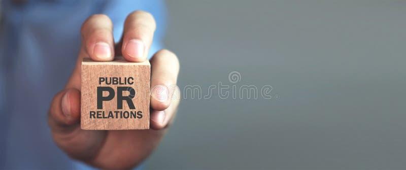 Человек держа деревянный куб Связи с общественностью pr стоковые фото