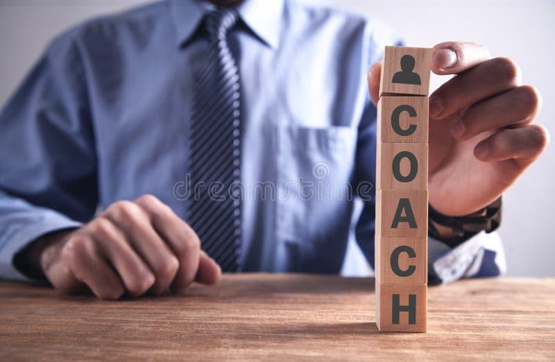 Человек держа деревянный куб со словом тренера r стоковое изображение